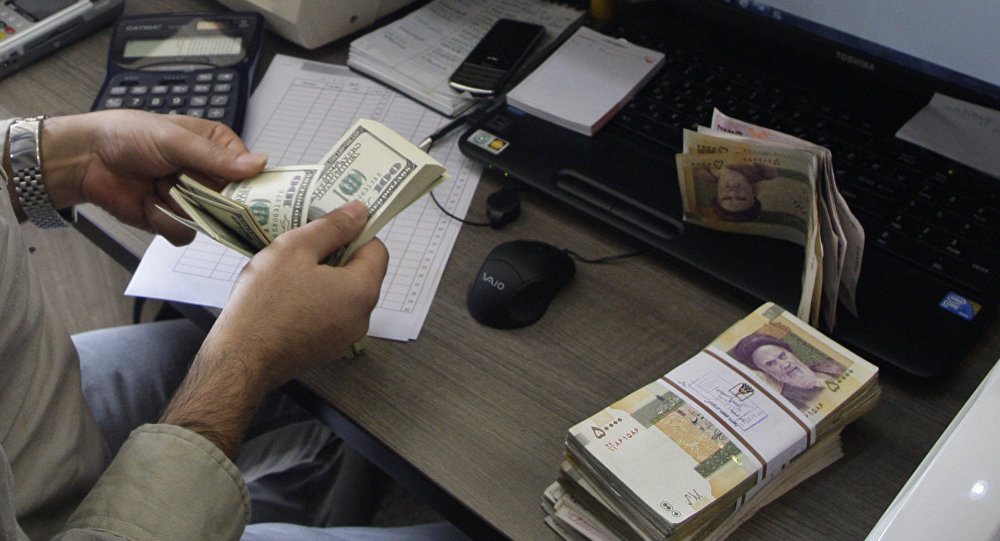 A currency exchange bureau worker counts US dollars, as Iranian bank notes are seen at right with portrait of late revolutionary founder Ayatollah Khomeini.