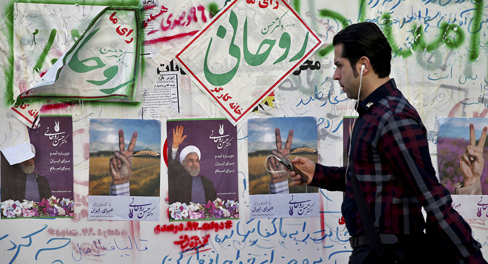 In this Wednesday, May 10, 2017 photo, an Iranian man walks past electoral posters and hand written slogans for presidential election candidates in downtown Tehran, Iran