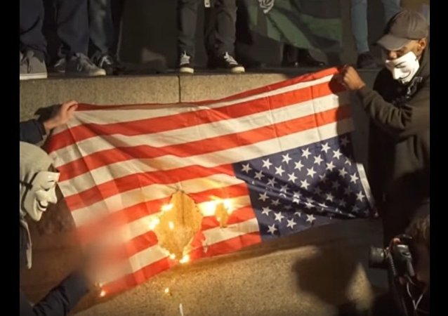 Londoners burn the US flag at the Million Mask March